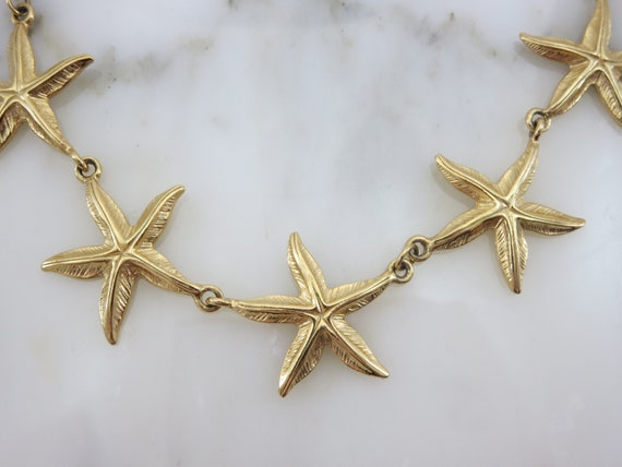 Good Condition. Chunky Chain Gold Tone Starfish Necklace with Lucite Light Green Sparkly Stones and Gold Tone Sand Dollar Medallions