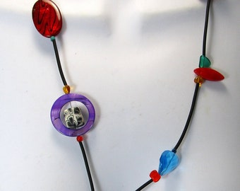 Malia, red, blue , green, purple, black rubber, rope style, front magnetic closure,  textured,  asymmetrical,