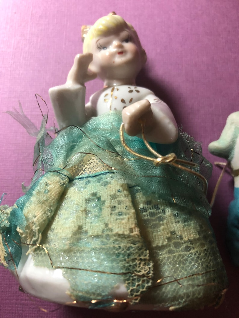 She is wearing a blue lace dress Vintage Antique  Girl figurine with blue poodle 50s era.