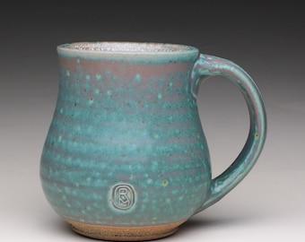 handmade pottery mug with green and white glazes