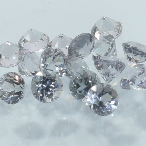 One White Sapphire Faceted 3 mm Diamond Cut Round Accent Gem Averages .13 carat