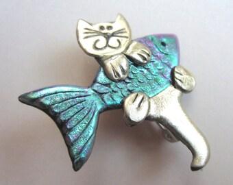 Cat holding an iridescent Fish Pin Brooch