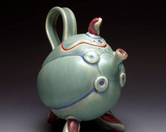 Green Teapot, a whimsical ceramic teapot with tripod base, rattle lid