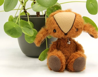 Fluffy brown doll with teddy bear necklace