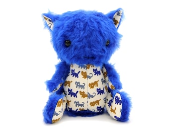 Fluffy blue soft toy with cat print