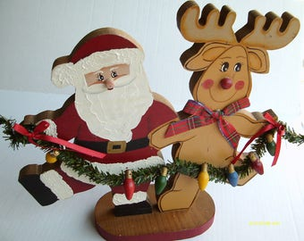 Wooden Santa and Rudolph the Red Nosed Reindeer holding a christmas tree light strand, 11.5 by 11.5 inches, Painted