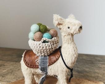 alpaca soft sculpture animal with basket of pom poms
