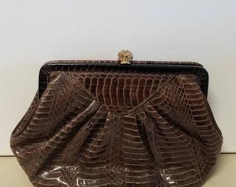 Luxurious brown Lyrella clutch with rhinestone snap clasp.