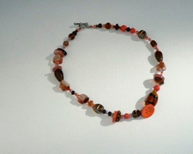Robot. Glass beads, crystal beads, buttons and resin beads in orange and brown tones.