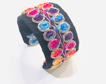 Candy. Cuff bracelet in a bold rainbow of colors on a black base.