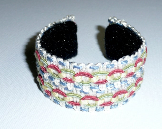 Danielle. Cuff bracelet made out of recycled upholstery trim in blue, coral, green and white.