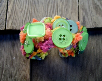 Green Tutifrutti, cuff bracelet made out of recycled pom-pom yarn and buttons in green tones.