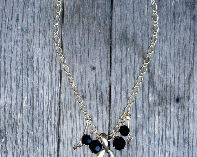 """Missing Link, gold tone letter initial """"O"""", acrylic faceted black beads, stars and a bell, on a gold plated chain necklace."""