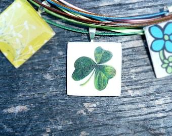 Trebol - Silver square resin pendant on a dark green wire.
