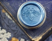 La Dame Blanche Solid Natural Perfume -  Round tin filled with a botanical synergy, featuring a signature, color coded honey bee wax seal