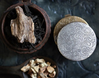 Figure 1: Noir Natural Solid Perfume in a Victorian Inspired Compact  A spellbinding, rich and loamy fragrance - Grounding, vital earth