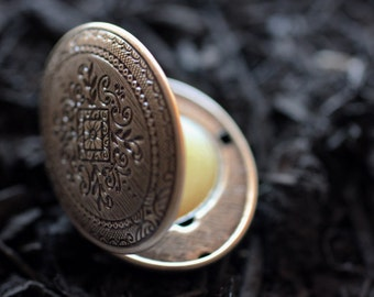 Figure 1: Noir Solid Natural Perfume Mini Compact  - A wet mossy earthiness that comes from a braid of leaves, roots and woods.