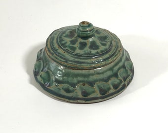Small hand-thrown and carved stoneware ring jar with pooled green glaze