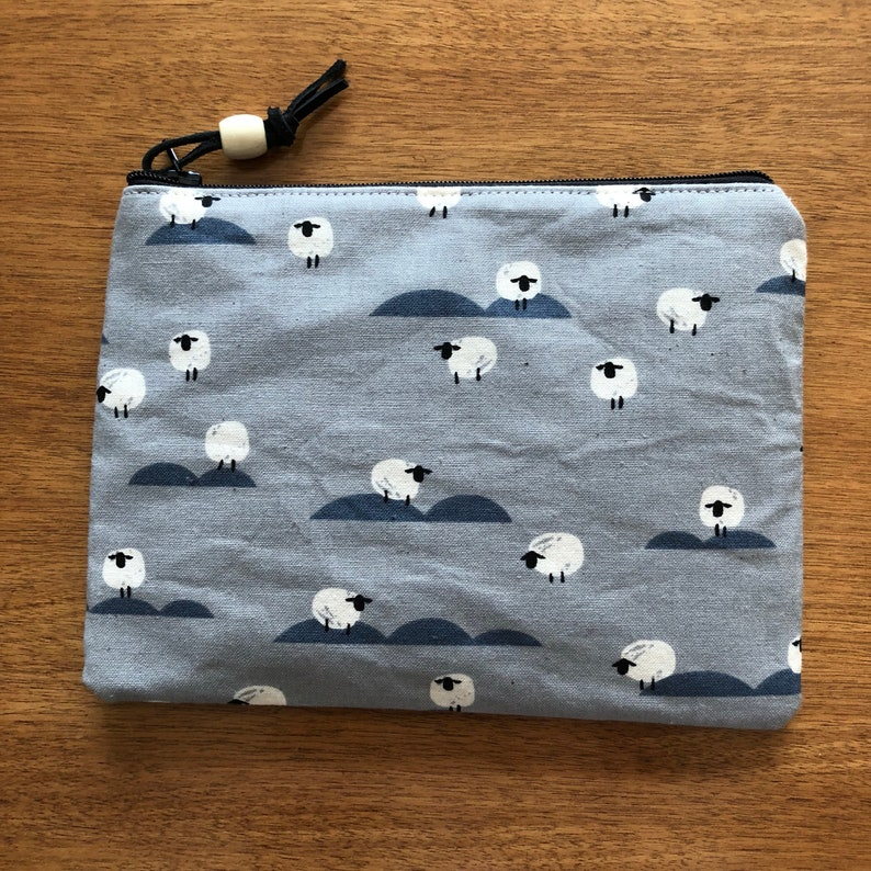 Sheep newspaper from the panorama cloue collection zippered pouch