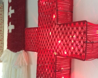 Large bright red cross in macramé