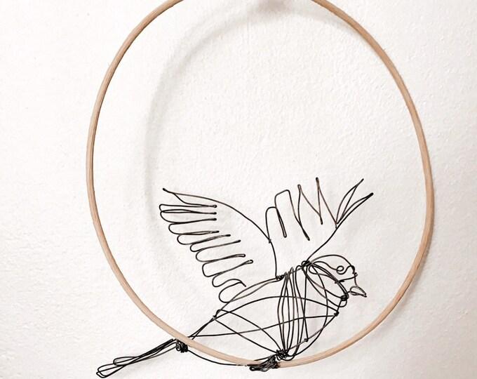 Wire bird. Black wire bird on a rattan perch. Animal sculpture, wire sculpture. Unique piece.