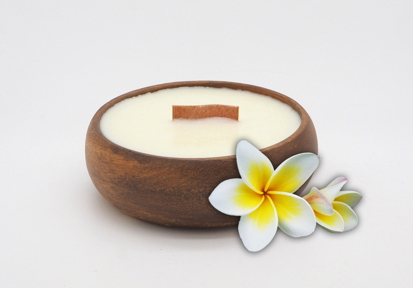 Soy plumeria-scented candle in a coconut shell