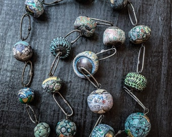 Long statement necklace with polymer clay art beads in shades of turquoise.