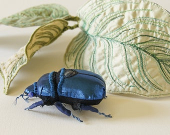 Blue jewel scarab with philodendron leaves textile sculpture