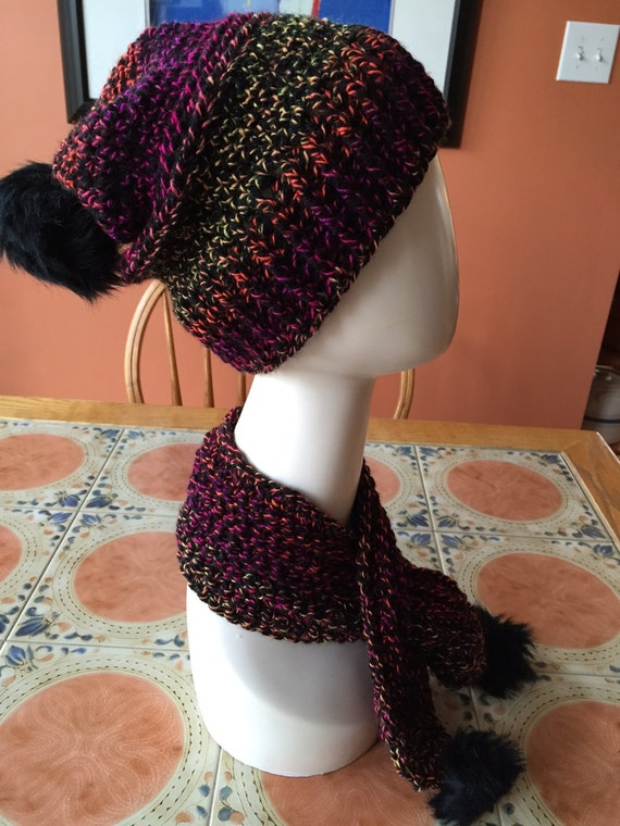 Black, fuchsia, orange tangerine, gold striped slouch hat with ribbed band and black faux fur pom with matching crossover neck scarf