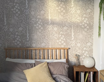 Hedgerow wallpaper in 'hush' by Hannah Nunn, a soft grey/pink botanical wall covering with a wild tangle of plants and flowers