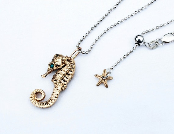 Solid 10k Yellow Gold Seahorse with Genuine Turquoise Eyes, hung on Sterling Silver Chain.