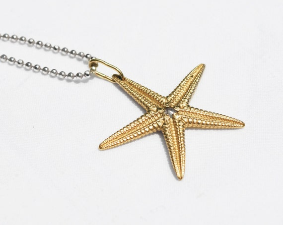 Large Solid 10k Yellow Gold Starfish Charm with Rose Cut Grey Diamond Center, hung on Sterling Silver chain with Gold Star detail.