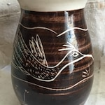 "Ceramic vase, Roadrunner design in a desert scene, underglaze, carved designs. 6""h x 4"" dia"