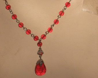 "1920's, 16"" long, necklace, with clear red beads on a silver metal chain"