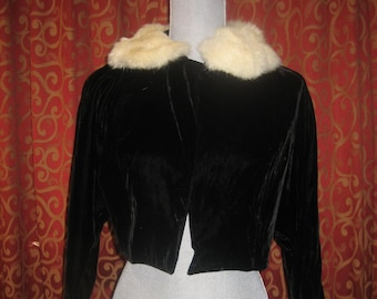 "1950's, 34"" bust, short black velvet jacket, with raglan sleeves, and a white mink collar."