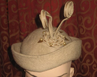 "1950's, size 22, oatmeal colored wool hat with turned up brim, narrow in front, with gold embroidered "" antenna"""