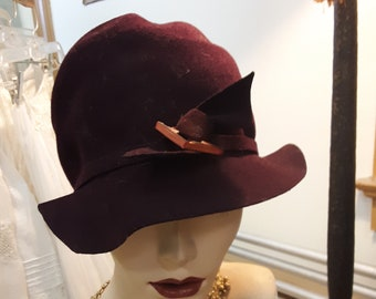 "1920s, 24""round, eggplant colored felt cloche hat"