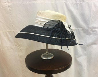 """1980s, size 22"""" , wide black brimed, white high crowned straw hat."""