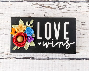 Love wins sign with rainbow felt flowers