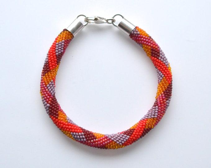 bracelet beaded braiding ornament red tones silver closure