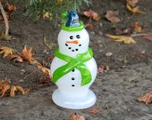 "Seattle Fan Glass Snowman Sculpture with Blue Hat and Green Scarf, Black Eyes & Smile, ""Carrot"" Nose, By Avalon Glassworks"