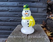 "Glass Snowman with Yellow and Green Hat and Yellow Scarf, Orange ""Carrot"" Nose with Black Eyes, Smile, Buttons, By Avalon Glassworks"