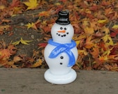 "Glass Frosty Snowman Sculpture with Black Hat, Blue Scarf, Black Eyes & Smile, ""Carrot"" Nose, By Avalon Glassworks"