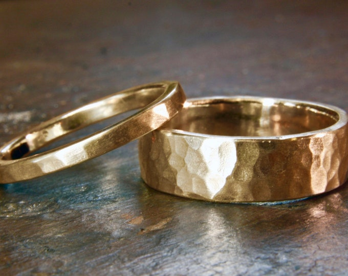 18 carat recycled yellow gold 6mm and 2mm wide hammered wedding rings. Matching unisex or his and hers. Hand made in the UK.