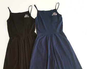 Breast pocket dress with removable gray striped handkerchief. Black or navy Ponte stretchy fabric. Adjustable straps. Square neckline.