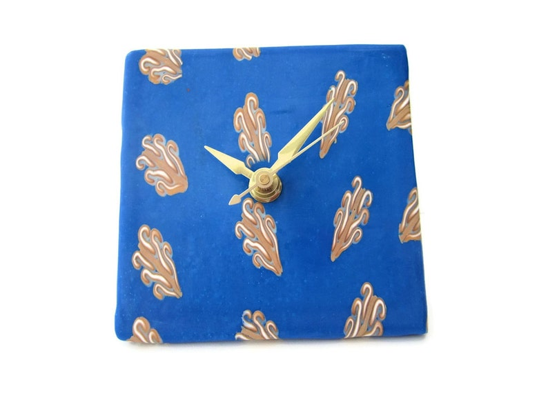 Battery Clock with Gold and White Reed Design on Blue Background Desk Clock