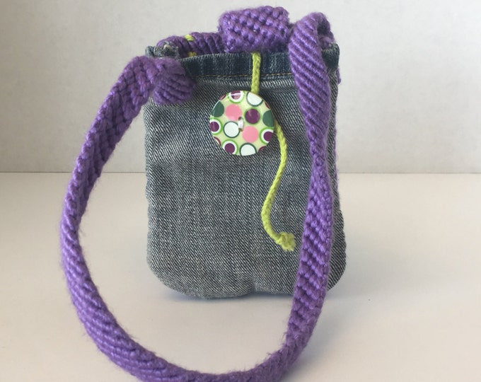 Woven wristlet with upcycled denim with button wrap closure. Purple and green acrylic yarn.