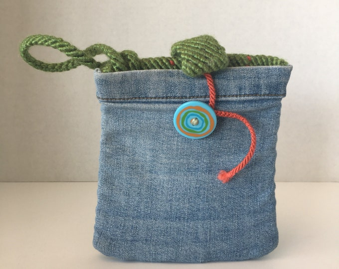 Hand woven wristlet with upcycled blue jeans. Green and orange, with button closure.
