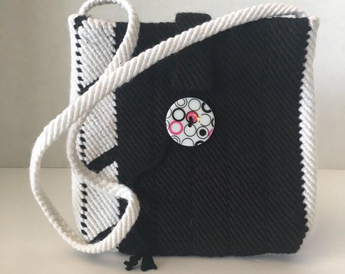 Woven, black and white Cotton purse with button closure.