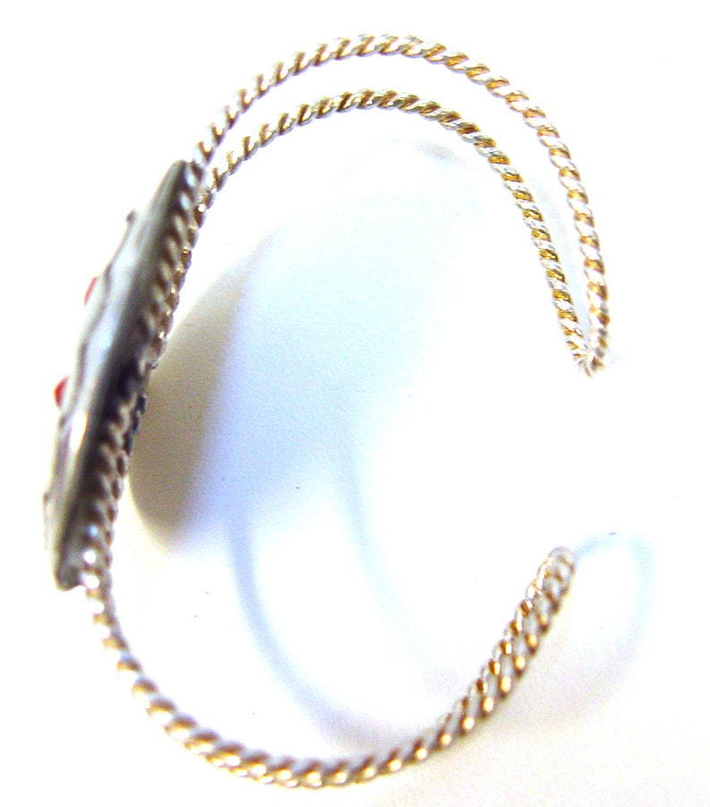 sterling silver twisted rope arms. Cuff bracelet with red coral shadowbox concho